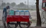 INDIA-WEATHER-MONSOON A street vendor covers himself and his cart with a plastic sheet to shelter from the rain in Allahabad on July 20, 2021. SANJAY KANOJIA / AFP