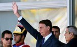 Brazilian President Jair Bolsonaro (C) waves next to his Defense Minister Braga Netto (R), and Navy Commander Almir Garnier (L), during a military vehicles parade in front of the Planalto Palace in Brasilia, on August 10, 2021. Bolsonaro is accused of using the armed forces for a show of force to intimidate National Congress, where a bill is being debated to modify the electronic voting system. EVARISTO SA / AFP
