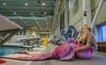 A mermaid puts on her silicone tail before entering the pool to take photos during MerMagic Con at the Freedom Aquatic Center in Manassas, Virginia on August 7, 2021. MerMagic Con is advertised as the largest Mermaid convention in the world. Some parts of the convention are based on modeling and looks like the Miss Mermaid USA Pageant. The Society of Fat Mermaids looks to bring together plus size people and promote the idea that anyone can become a mermaid. Becoming a mermaid is not cheap, most merfolk spend thousands of dollars on their tail and outfit. Most tails are custom made out of silicone and others are foam and fabric. Joseph Prezioso / AFP