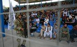 A Taliban fighter keeps vigil as spectators watch the Twenty20 cricket trial match being played between two Afghan teams 'Peace Defenders' and 'Peace Heroes' at the Kabul International Cricket Stadium in Kabul on September 3, 2021. Aamir QURESHI / AFP
