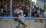 A Taliban fighter (C) walks past spectators watching the Twenty20 cricket trial match being played between two Afghan teams 'Peace Defenders' and 'Peace Heroes' at the Kabul International Cricket Stadium in Kabul on September 3, 2021. Aamir QURESHI / AFP