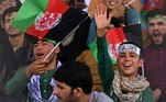 Spectators wearing Afghan and Taliban head ribbons watch the Twenty20 cricket trial match being played between two Afghan teams 'Peace Defenders' and 'Peace Heroes' at the Kabul International Cricket Stadium in Kabul on September 3, 2021. Aamir QURESHI / AFP