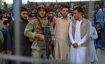 Spectators pose for pictures along with a Taliban fighter during the Twenty20 cricket trial match being played between the two Afghan teams 'Peace Defenders' and 'Peace Heroes' at the Kabul International Cricket Stadium in Kabul on September 3, 2021. Aamir QURESHI / AFP