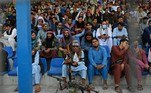 A Taliban fighter (C) keeps vigil as spectators watch the Twenty20 cricket trial match being played between two Afghan teams 'Peace Defenders' and 'Peace Heroes' at the Kabul International Cricket Stadium in Kabul on September 3, 2021. Aamir QURESHI / AFP