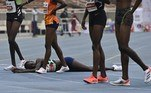 Margaret Chelimo (bottom) lays on the track after competing in the 5000M women finals race during the trials for the Tokyo Olympic games at the Kasarani stadium in Nairobi on June 17, 2021. Simon MAINA / AFP