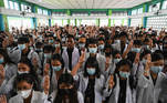 Members of the medical community hold up the three finger salute at the funeral of Khant Nyar Hein at his funeral in Yangon on March 16, 2021, after the first year medical student was shot dead during a crackdown by security forces on protesters taking part in a demonstration against the military coup. STR / AFP