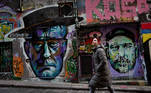People walk past artworks in Melbourne's Hosier Lane on June 24, 2021 where street artists are able to paint at will, creating a tourist attraction in the city. William WEST / AFP