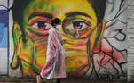 A woman wearing a raincoat walks past a mural depicting a woman with a facemask to spread awareness about the Covid-19 coronavirus, in Mumbai on June 17, 2021. Punit PARANJPE / AFP