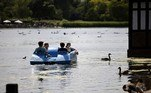 People ride in a pedalo in the sunshine in Hyde Park in London on June 14, 2021. Britain was on Monday widely expected to delay the full lifting of coronavirus restrictions due to a surge of infections caused by the Delta variant. Tolga Akmen / AFP