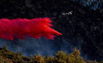 An airplane drops fire retardant on the Springs Fire as it burns along a hillside in the Angeles National Forest in Valyermo, California, April 5, 2021. Kyle Grillot / AFP
