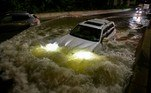 A motorist drives a car through a flooded expressway in Brooklyn, New York early on September 2, 2021, as flash flooding and record-breaking rainfall brought by the remnants of Storm Ida swept through the area. Ed JONES / AFP