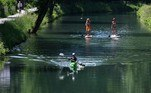 A man kayaks in front of stand-up paddlers on the Lend canal in Klagenfurt, Austria on June 17, 2021. BARBARA GINDL / APA / AFP