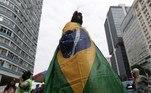 AME2723. RÍO DE JANEIRO (BRASIL), 07/09/2021.- Una mujer arropada en una bandera brasileña participa en las marchas a favor y en contra del presidente de Brasil, Jair Bolsonaro, hoy, día de la Independencia brasileña, en Río de Janeiro (Brasil). Además de manifestaciones convocadas por la extrema derecha, grupos de oposición también salen a las calles este martes, cuando Brasil celebra el aniversario de su independencia. EFE/ André Coelho