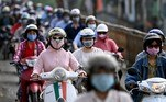 Morning commuters wearing face masks, amidst concerns about the Covid-19 coronavirus, ride past in Hanoi on May 4, 2021. Manan VATSYAYANA / AFP