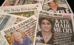"""An arrangement of UK daily newspapers photographed as an illustration in Brighton on March 8, 2021, shows front page headlines reporting on the story of the interview given by Meghan, Duchess of Sussex, wife of Britain's Prince Harry, Duke of Sussex, to Oprah Winfrey, which aired on US broadcaster CBS. Prince Harry and his wife Meghan's explosive tell-all interview with Oprah Winfrey went much further than expected and will be hugely damaging to the royal family, British media said Monday. The Duke and Duchess of Sussex, as they are formally known, delivered """"enough bombshells to sink a flotilla"""", reported The Daily Telegraph, as the dust settled on the broadcast in the United States on Sunday night. Glyn KIRK / AFP"""