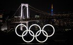 A general view shows the Olympic rings lit up at dusk, with the Rainbow bridge and the Tokyo Tower (back R) in the background, on the Odaiba waterfront in Tokyo on May 10, 2021. Charly TRIBALLEAU / AFP