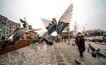A woman wearing a face mask passes by flying pigeons in central Moscow on April 1, 2021. Yuri KADOBNOV / AFP