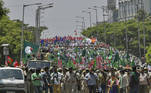 Police personnel march in front of activists of pro-farmer organisations during a protest rally supporting the ongoing farmers' protest against the central government's recent agricultural reforms, in Bangalore on March 22, 2021. Manjunath Kiran / AFP
