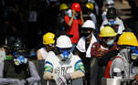 Protesters wearing protective gears and carrying homemade shields gather along a street during a demonstration against the military coup in Yangon on March 9, 2021. STR / AFP