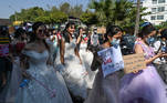 Myanmar women in wedding gowns holds up placards during a demonstration against the February 1 military coup in Yangon on February 10, 2021. Ye Aung THU / AFP