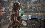 A woman seeks shelter during a downpour in Dhaka on June 21, 2021. Munir Uz zaman / AFP