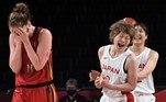 Japan's Maki Takada (C) and Yuki Miyazawa celebrate their win as Belgium's Emma Meesseman (L) reacts in the women's quarter-final basketball match between Japan and Belgium during the Tokyo 2020 Olympic Games at the Saitama Super Arena in Saitama on August 4, 2021. Aris MESSINIS / AFP