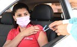 A woman receives a jab of the CoronaVac COVID-19 vaccine from a healthcare worker at a drive-thru vaccination post in Brasilia on September 13, 2021. Brazil is one of the fastest vaccinating countries on the planet, after a late and chaotic start that continues to take its toll on President Jair Bolsonaro. EVARISTO SA / AFP