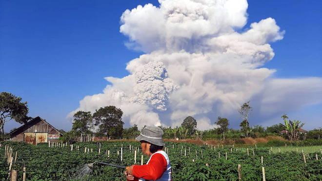 Uma fazendeira da região trabalha normalmente enquanto as cinzas do vulcão do Monte Sinabung, na Indonésia, dominam os céus de Karo, ao norte da ilha de Sumatra neste terça-feira (2)