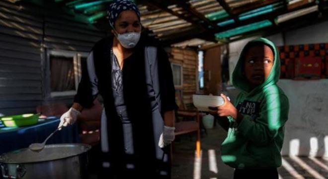 Menino é alimentado por cozinheira de programa comunitário em meio à pandemia