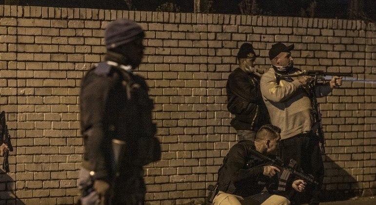 Policial observa grupo de seguranças fortemente armados nas ruas de Johannerburgo