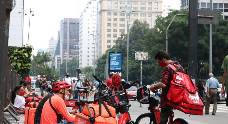 Entregadores de app esperam os pedidos na Avenida Paulista