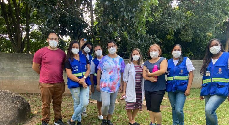 De avental branco, Julie atende moradores da Brasilândia ao lado de agentes de saúde
