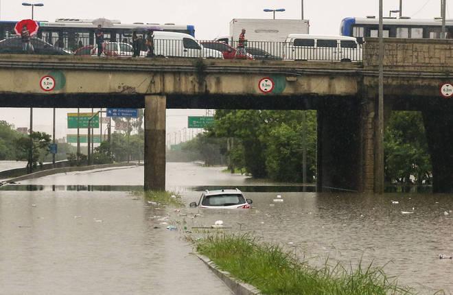 Carro fica quase todo submerso em ponto de alagamento sob a Ponte da Casa Verde, na zona norte de São Paulo, na manhã desta segunda-feira (10)