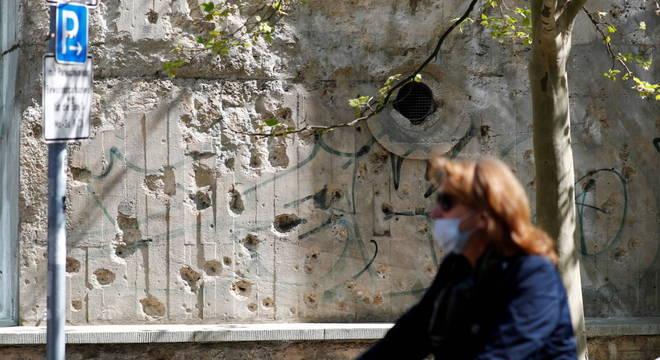 Mulher de máscara passa em frente a muro com marcas das batalhas em Berlim há 75 anos: na Alemanha, medidas contra coronavírus foram comparadas a guerra