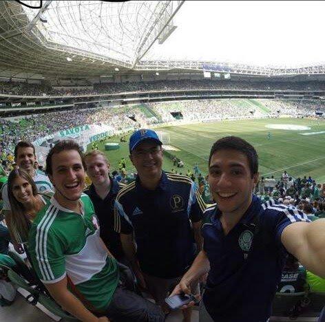 Uma foto de torcedores muito alegres. Com o distintivo do Palmeiras no peito