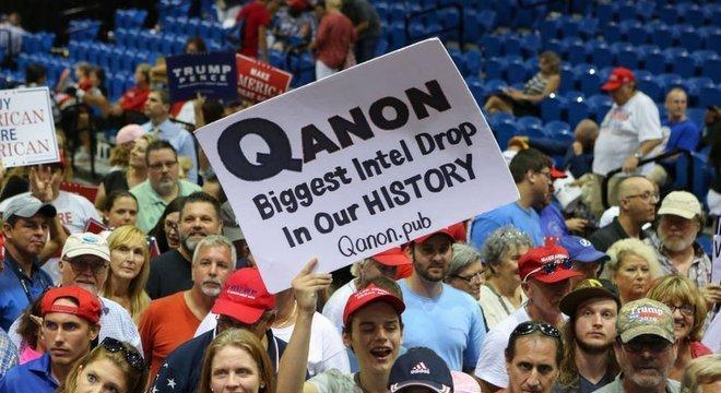 Apoiadores exibindo pôsteres do QAnon apareceram nos comícios de Trump no verão passado