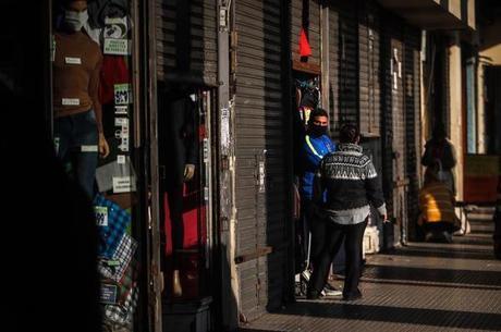 Homem espera a chegada de clientes em frente a sua loja