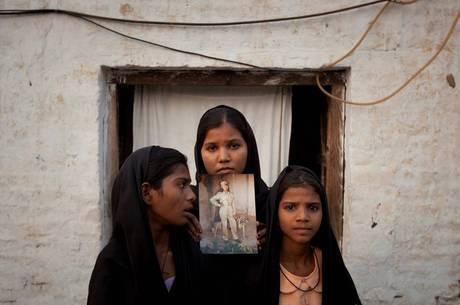 As filhas de Asia Bibi segurando uma foto da mãe