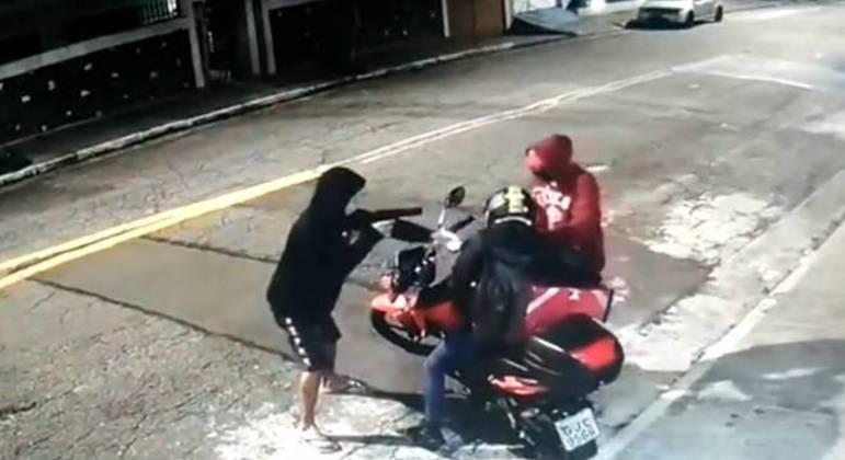Um dos suspeitos retira a mulher a força da moto