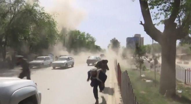 Três pessoas fogem de segunda explosão em Cabul nesta segunda-feira, que matou 9 jornalistas