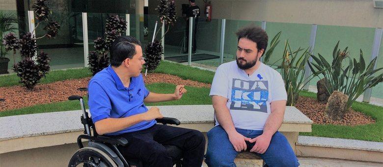 Thiago Helton conversando com um rapaz autista