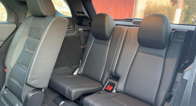 Segunda fileira conta com sistema de acionamento por botão para ter acesso ao fundo do veículo onde dois adultos não muito altos até que viajam de forma confortável