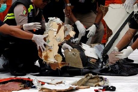 Funcionários de resgate coletam destroços do avião