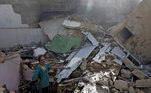 Um homem sobre os destroços de uma casa no local da queda de avião da PIA Airlines em Karachi