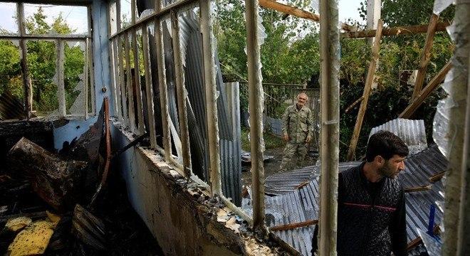 Moradores inspecionam casa atingida por um foguete na vila de Baharli