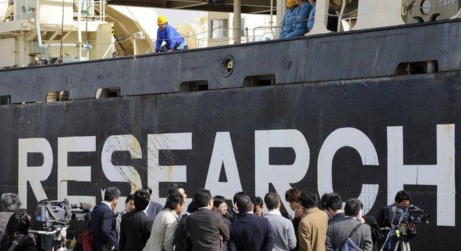 Jornalistas em frente a navio japonês para captura de baleias em 1980