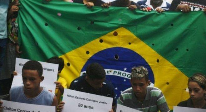 Bandeira do Brasil com buracos representa tiros de 111 balas disparadas pela polícia contra 5 jovens no Rio, em 2015