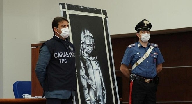 Policiais ao lado de mural atribuído ao artista Banksy recuperado na Itália