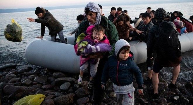 Imigrantes do Afeganistão chegam em um bote em praia da Ilha de Lesbos