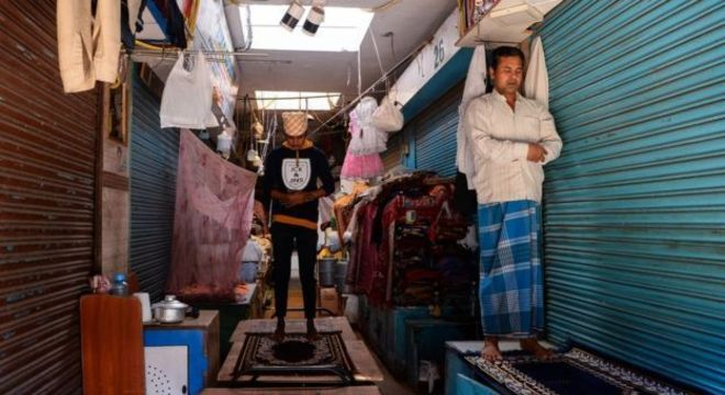 Muçulmano reza em frente ao comércio fechado em Nova Déli durante o Ramadã